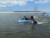 まずは一人づつ波をすべる感覚を体感。その後、ボードの上に立ち上がる練習を繰り返します。
